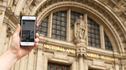 phone displaying natural history museum instagram account outside victoria and albert museum