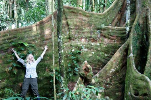 Photo of Beulah stood with her arms outstretched and dwarfed by the root system of a Ficus tree