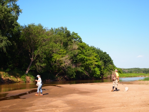 Photo showing Mary and Oliver walking and collecting on a mud bank beside a river