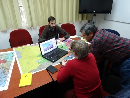 Photo showing the three volcanologists seated with maps and PC on a table in front of them, discussing places to go.