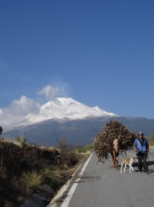 Photo showing the three walking along a road, with the volcano in the background