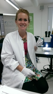 Photo showing Chloe seated holding a slide while wearing a lab coat