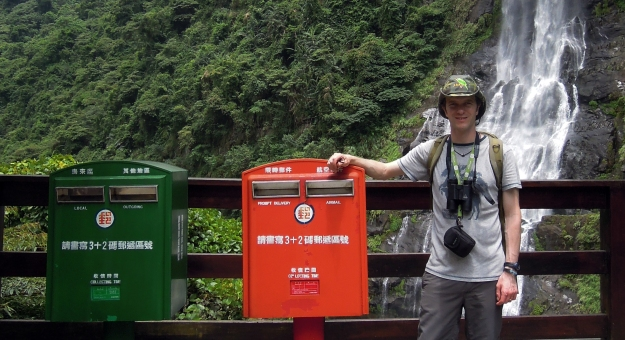 Photo showing Joe in the far east standing in front of a waterfall beside two post boxes, one red and one green