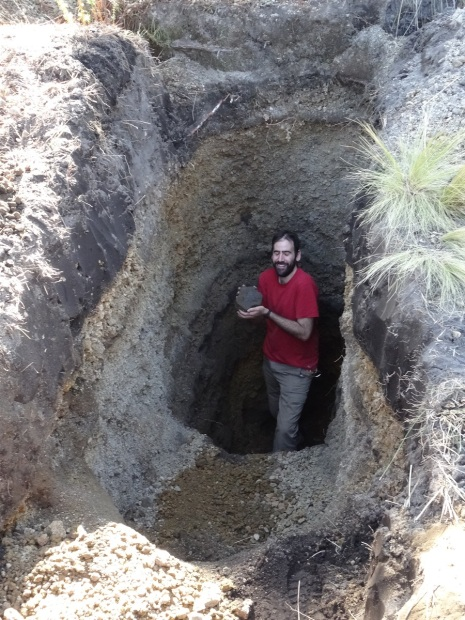 Photo of Guillem standing at the bottom of the hole, holding a piece of the lava flow in his hands and smiling