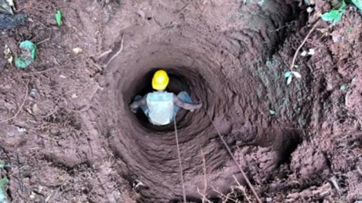 Man climbing down pit