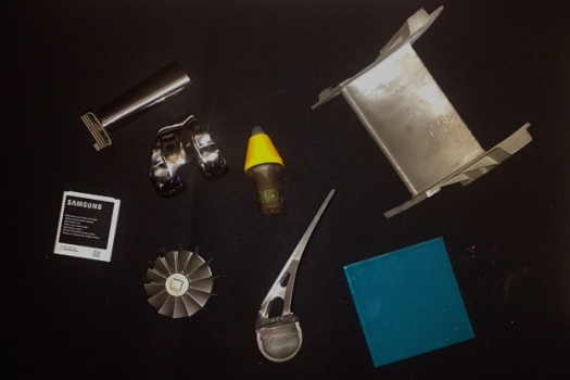 Items on a table including a phone battery and a turbine