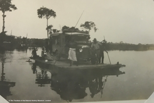 Black and white archival photo showing a Dodge van being transported on a raft down a river, with 4 men steering the craft with long poles and oars, and the owner of the vehicle posing in front