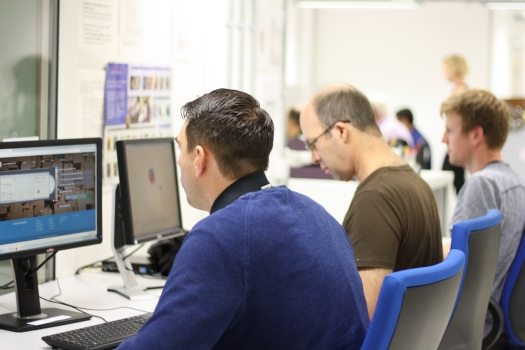 Photo showing volunteers sitting at computers entering data