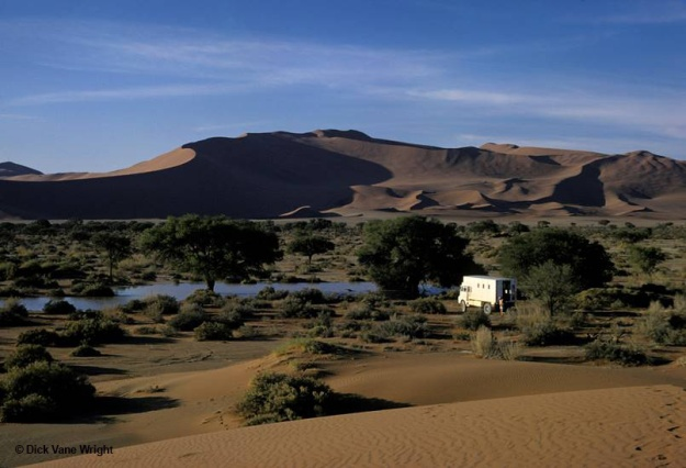 Colour archival photograph showing a white truck in the mid-distance, parked in sparsely vegetated bushland next to a watering hole, with sand dunes rising from the horizon in the background