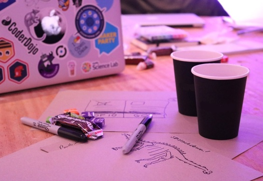 Photo showing pens and paper, laptop, sweets and coffee cups on a desk with sketches of ideas on the paper
