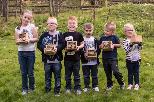 Photo of six children in a line holding their insect hotels and smiling.